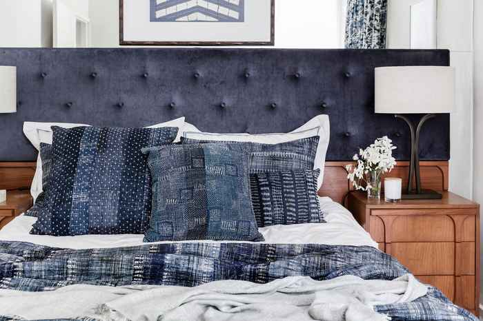 masculine bedroom navy blue pillows headboard linens classic interior design